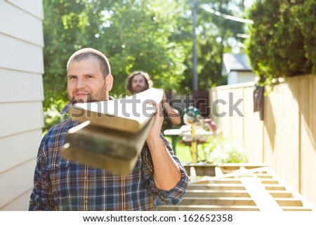 Portrait of male carpenter and coworker carrying lumbers at construction site