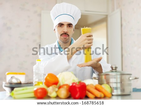Portrait of male caucasian cook in uniform with pasta at kitchen - stock photo