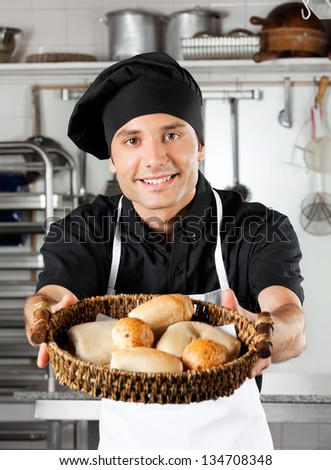 Portrait of male chef offering baked breads in commercial kitchen counter