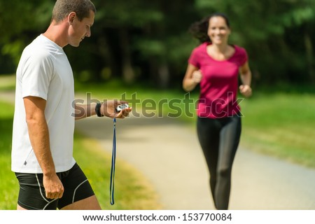 Portrait of male coach timing runner in a park - stock photo
