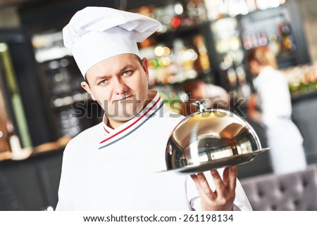 portrait of male cook chef at restaurant serving food with cloche lid - stock photo