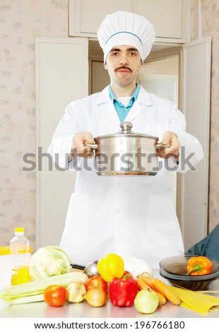 Portrait of male cook in toque with pan at kitchen - stock photo