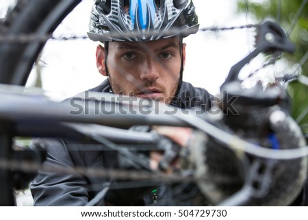 Portrait of male cyclist repairing his mountain bike in park