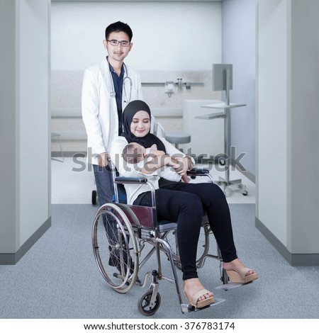Portrait of male doctor pushing a young mother and her baby with a wheelchair in the hospital