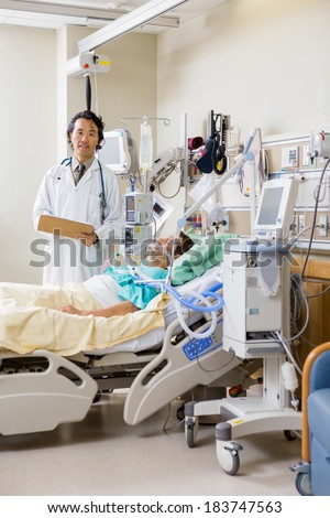Portrait of male doctor with patient's report standing by bed in hospital room