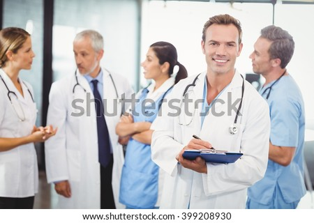 Portrait of male doctor writing on clipboard and colleagues standing behind and discussing in hospital - stock photo