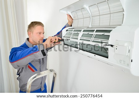Portrait Of Male Electrician Repairing Air Conditioner Standing On Stepladder - stock photo
