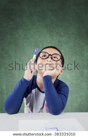 Portrait of male elementary school student holds a pen and thinking idea while sitting in the classroom - stock photo