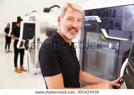 Portrait Of Male Engineer Operating CNC Machinery In Factory