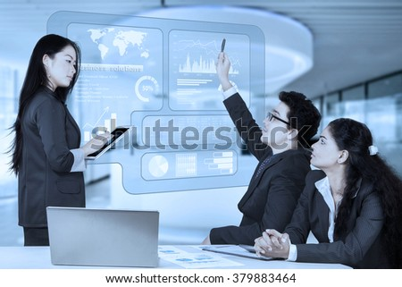 Portrait of male entrepreneur asking a question to a businesswoman during a presentation in the office - stock photo