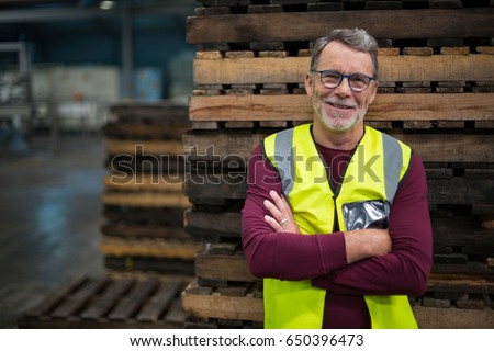 Portrait of male factory worker standing with arms crossed in drinks production factory