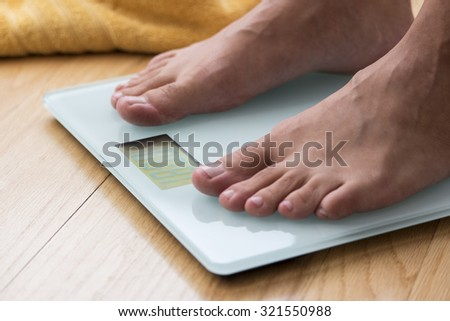 Portrait of male feet on a scale - stock photo