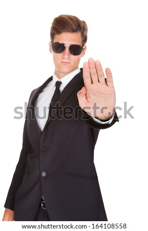 Portrait Of Male Guard In Suit Gesturing Stop Sign On White Background - stock photo