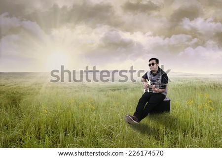 Portrait of male guitarist sitting on amplifier in the meadow while playing guitar - stock photo