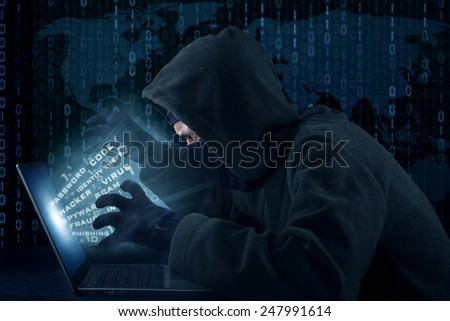 Portrait of male hacker wearing black mask and stealing user identity - stock photo