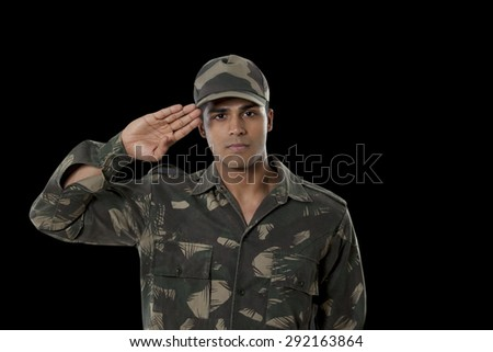 Portrait of male Indian soldier saluting over black background - stock photo