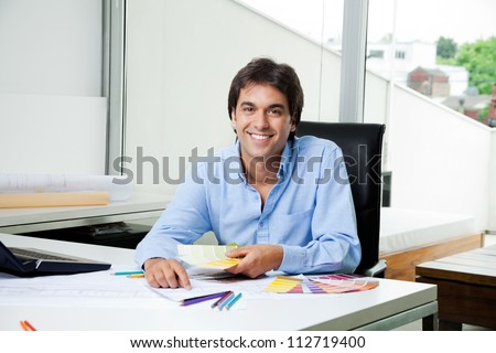 Portrait of male interior designer working at office with color swatches - stock photo