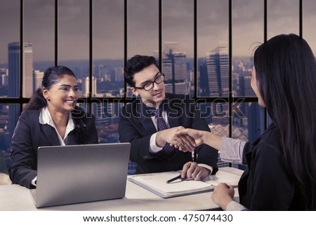 Portrait of male interviewer and his partner shaking hands with new female employee in the office