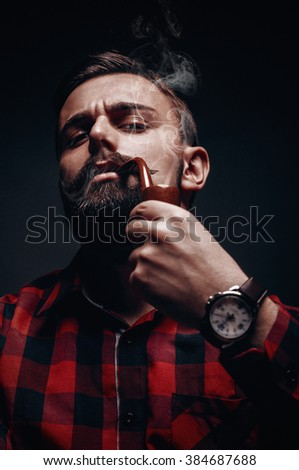 Portrait of male lumber jack model with beard and mustache smoking pipe