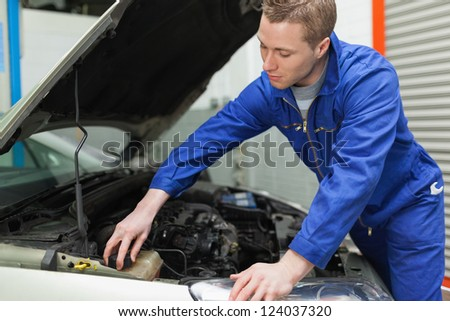 Portrait of male mechanic closing the lid of windshield washer tank - stock photo
