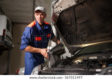 Portrait of male mechanic fixing car engine in repair shop