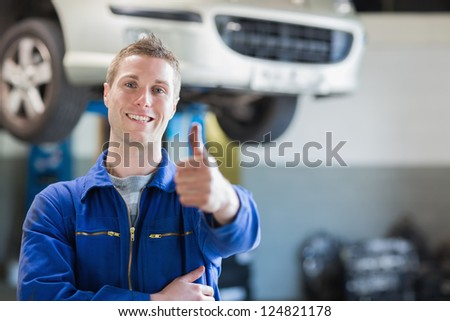 Portrait of male mechanic giving thumbs up in workshop - stock photo