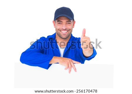 Portrait of male mechanic with blank placard gesturing thumbs up on white background - stock photo