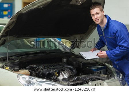 Portrait of male mechanic with clipboard analyzing car engine - stock photo
