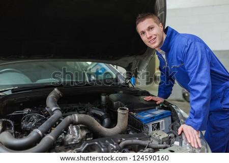 Portrait of male mechanic working under car bonnet - stock photo