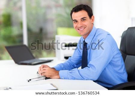 portrait of male medical doctor in office - stock photo