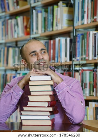 Portrait of male middle eastern student sitting at desk in Begen city library with a pile of books