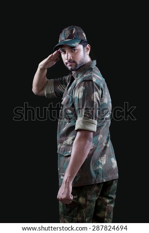 Portrait of male military soldier saluting - stock photo
