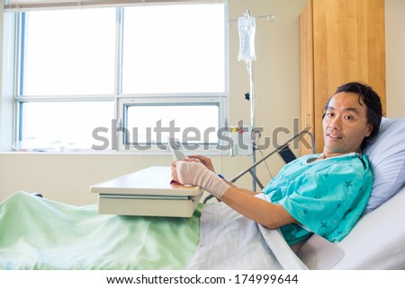 Portrait of male patient holding digital tablet while reclining on bed in hospital - stock photo