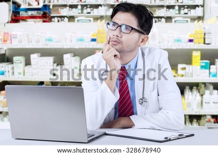 Portrait of male pharmacist sitting in the drugstore and looks thinking something while holding his chin - stock photo