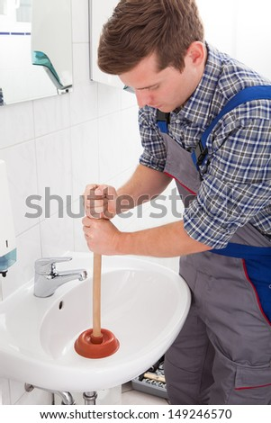 Portrait of male plumber pressing plunger in sink - stock photo