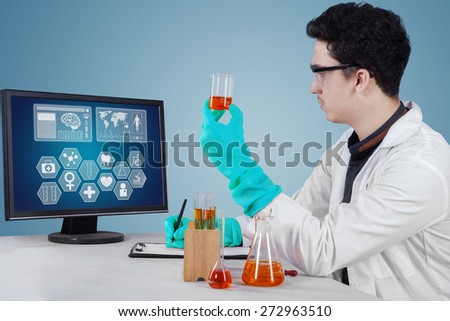 Portrait of male researcher doing experiment with liquid chemical in the laboratory - stock photo
