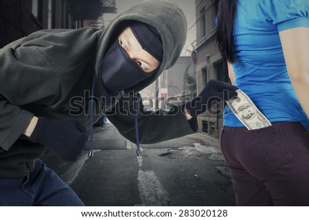 Portrait of male robber wearing mask and black jacket, stealing money from pocket of his victim at the street - stock photo