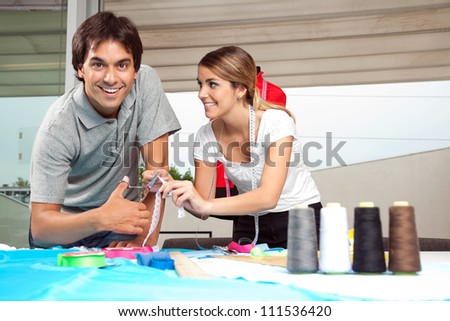 Portrait of male tailor with female assistant cutting ribbon