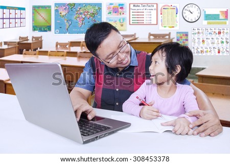 Portrait of male teacher talking with female elementary school student in the classroom while helping her to study - stock photo