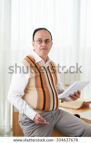 Portrait of male teacher with textbook and pen