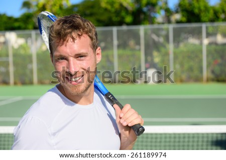 Portrait of male tennis player holding tennis racket after playing at game outside on hard court in summer. Fit man sport fitness athlete smiling happy living healthy active lifestyle outside. - stock photo