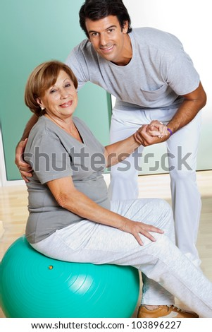 Portrait of male therapist helping senior woman sitting on fitness ball