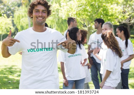 Portrait of male volunteer pointing at tshirt with friends in background - stock photo