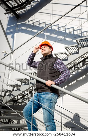 Portrait of male worker in hardhat standing on steel staircase - stock photo