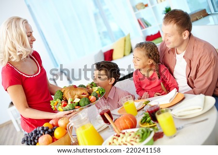 Portrait of man and two kids looking at roasted turkey held by happy female - stock photo