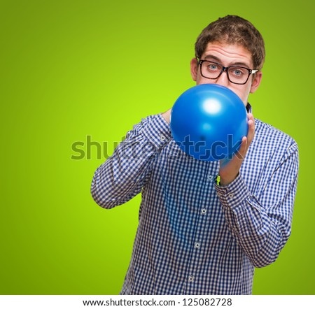 Portrait Of Man Blowing Blue Balloon against a green background