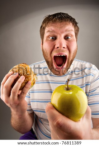 Portrait of man choosing between hamburger and green apple - stock photo