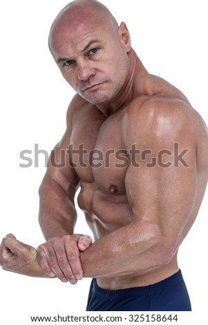 Portrait of man flexing muscles against white background - stock photo