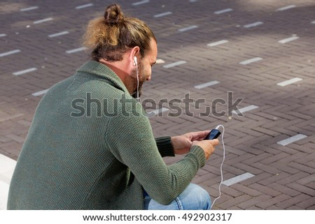 Portrait of man from behind listening to music on smart phone