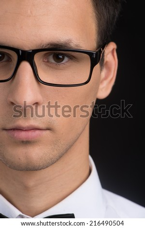 Portrait of man half face looking at camera. man wearing black fashion glasses - stock photo
